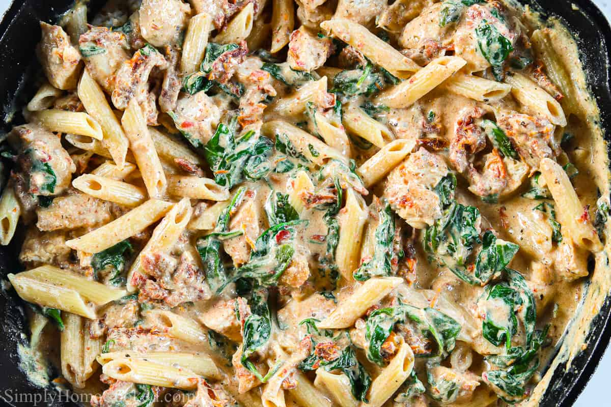 Close up of Creamy Tuscan Chicken Pasta in a cast iron skillet.