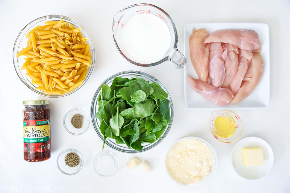 Ingredients to make Creamy Tuscan Chicken Pasta, including penne pasta, fresh spinach, heavy cream, chicken, sun dried tomatoes, oil, butter, parmesan cheese, garlic, salt, pepper, and Italian seasoning.