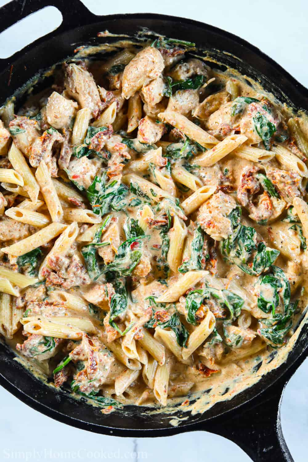 Creamy Tuscan Chicken Pasta in a cast iron skillet.