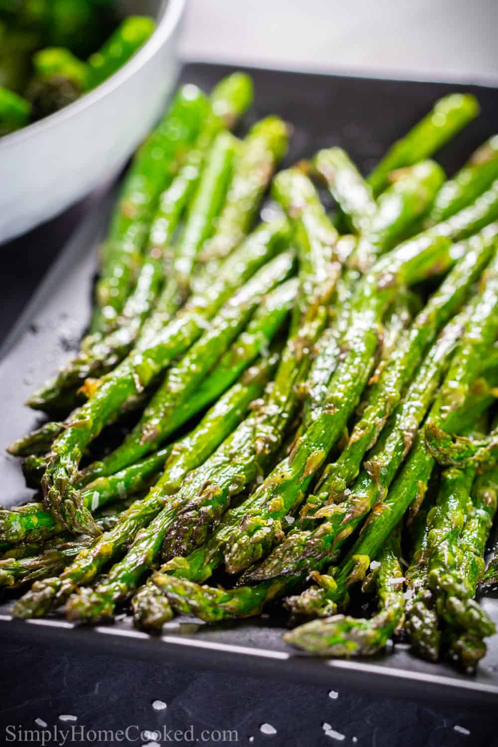 Air fried asparagus spears lined up on a plate.