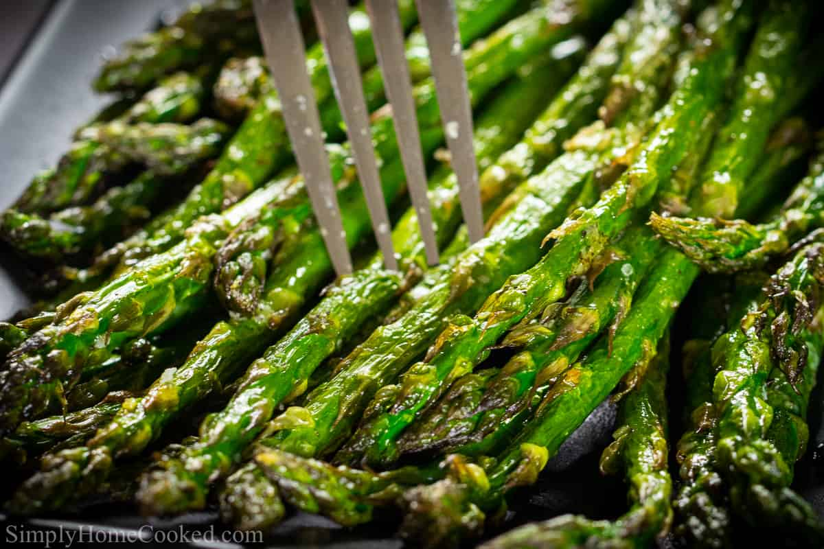Close up of fork in plate full of asparagus spears.