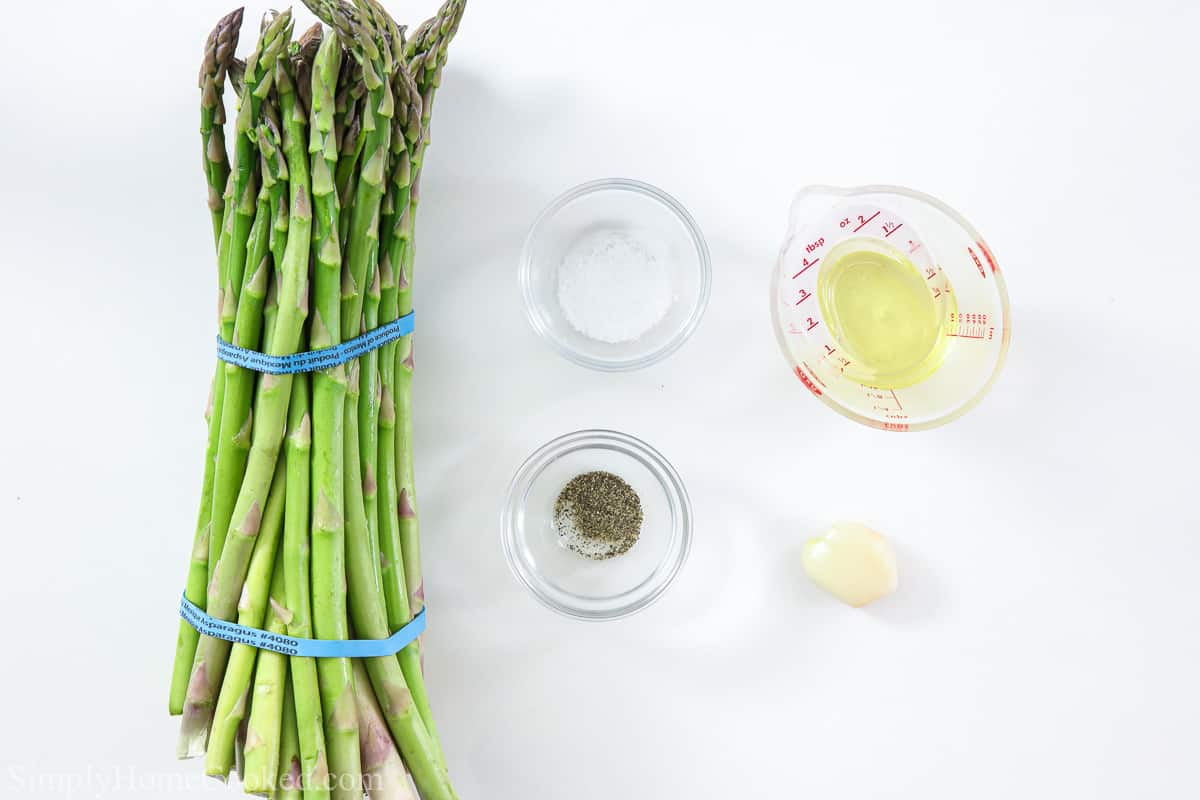 Ingredients for air fryer asparagus, including asparagus spears, garlic, oil, salt, and pepper.