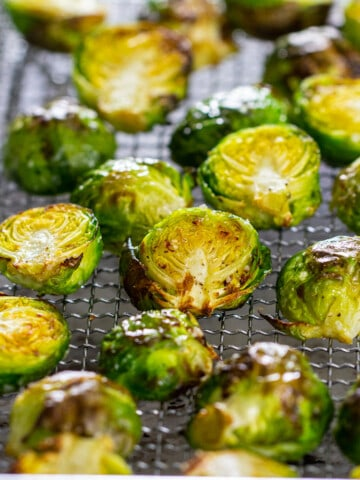 Brussels sprout halves that are crispy and laying on a wire rack