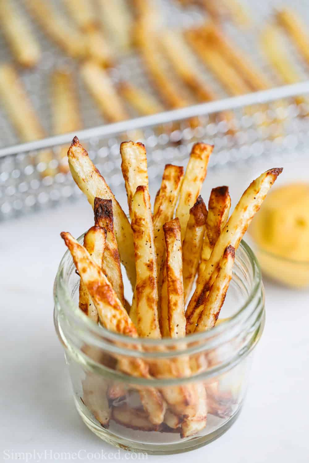 Air Fryer French fries in a jar with other fries and a dipping sauce in the background.