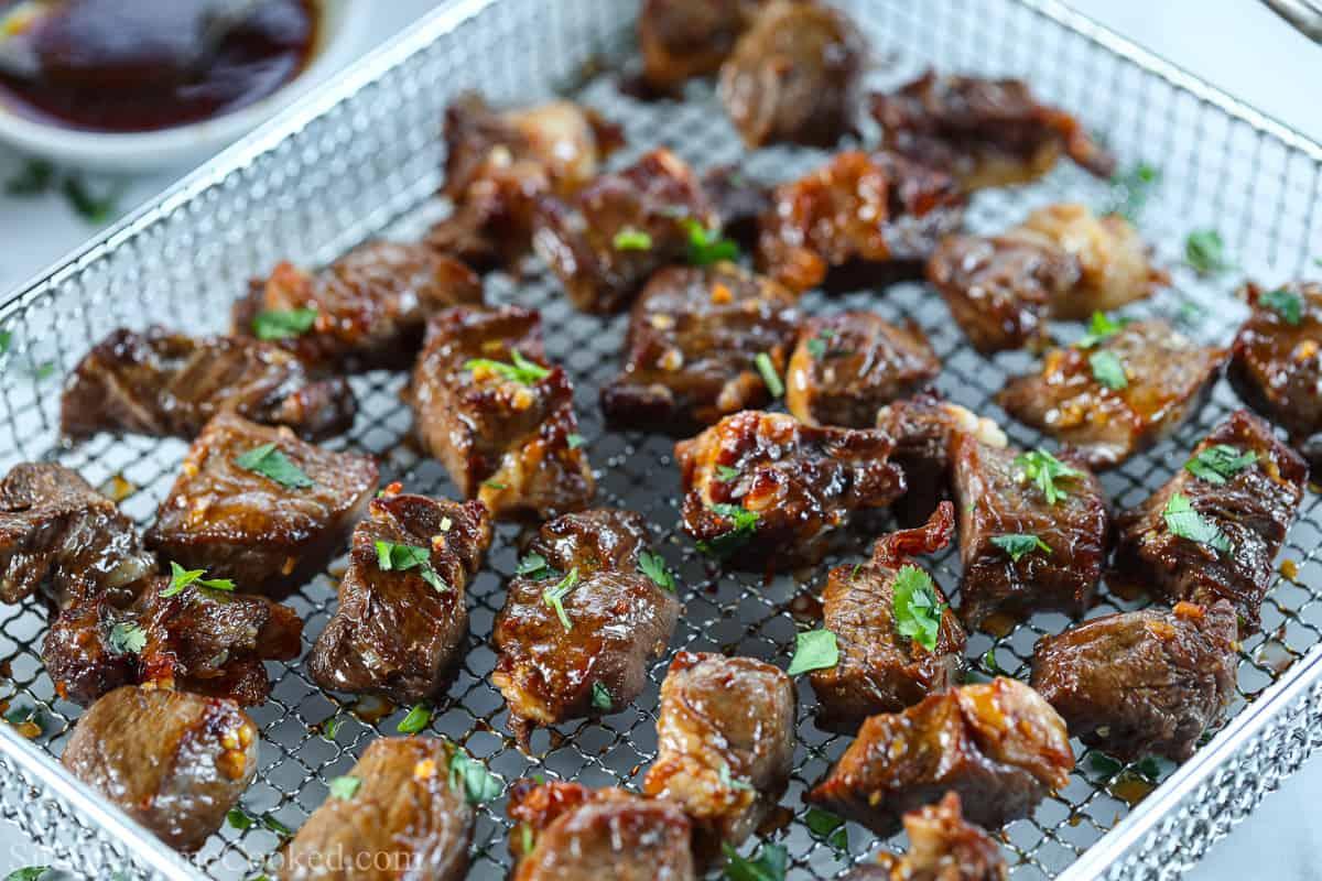 Air Fryer basket full of steak bites.