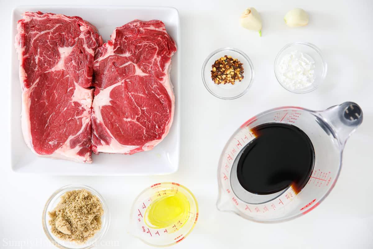 Ingredients for Juicy Air Fryer Steak Bites, including ribeye steak, brown sugar, soy sauce, corn starch, red pepper flakes, garlic, and salt.
