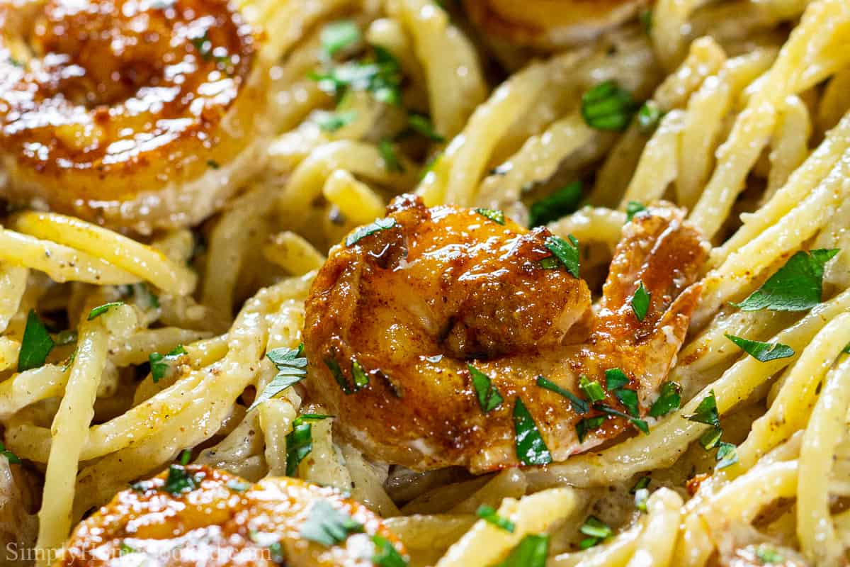 Close up of cajun shrimp in pasta with a cream sauce.