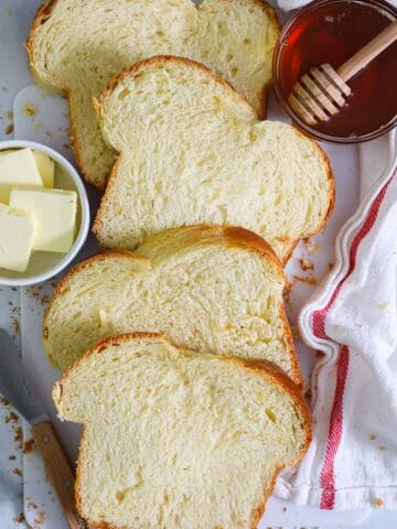 Slices of Buttery Brioche Bread laying on a white towel with butter and honey nearby.