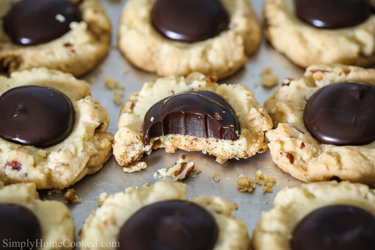 Close up of Chocolate Thumbprint Cookies lined up on a sheet pan, and one with a bite missing.