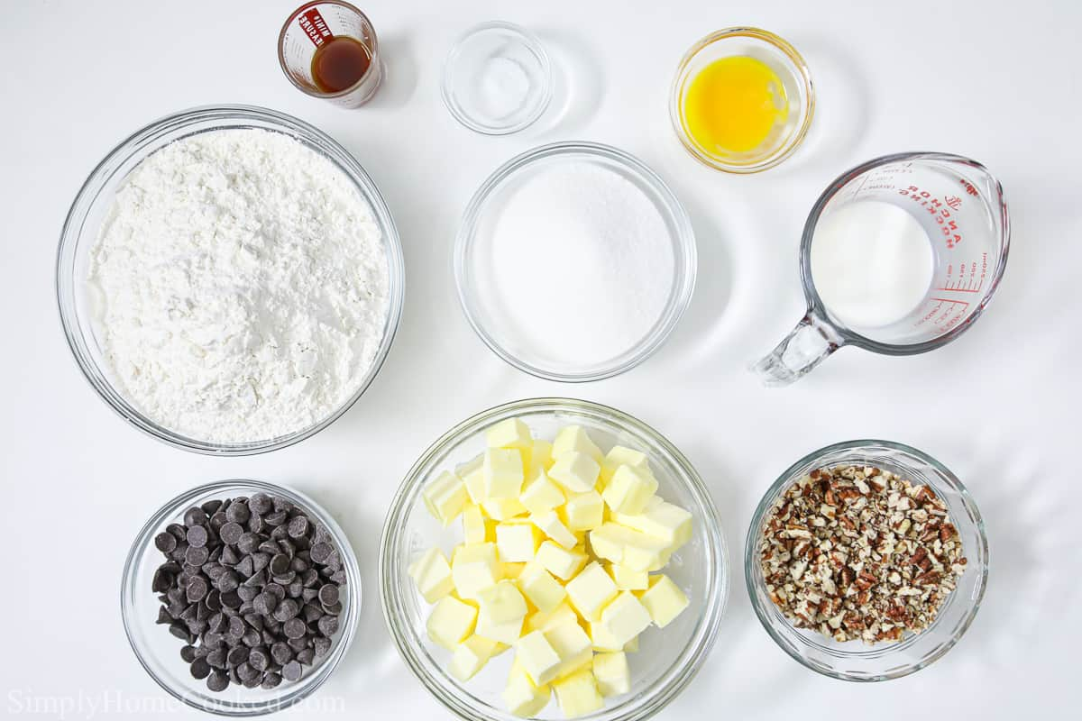 Ingredients for Chocolate Thumbprint Cookies, including butter, flour, sugar, chocolate chips, vanilla extract, egg yolks, cream, and toasted pecans.