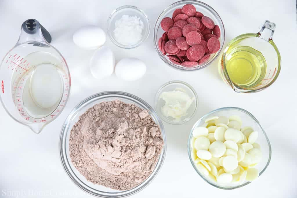 Ingredients for Red Velvet Cake balls, including red velvet cake mix, red and white candy melts, eggs, oil, water, dipping aid, and frosting.