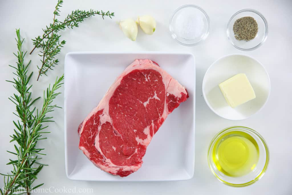 Ingredients for cast iron ribeye steak, including ribeye steak, rosemary and thyme sprigs, garlic cloves, butter, avocado oil, and salt and pepper.