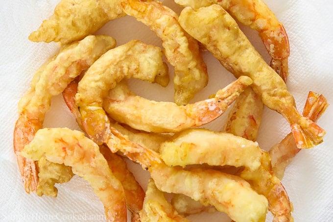 Shrimp tempura in a pile on a white background.