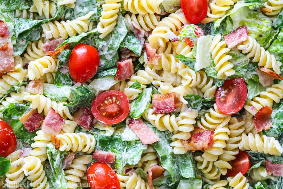 BLT Pasta Salad with cherry tomatoes, rotini, lettuce, chopped bacon, and dressing.