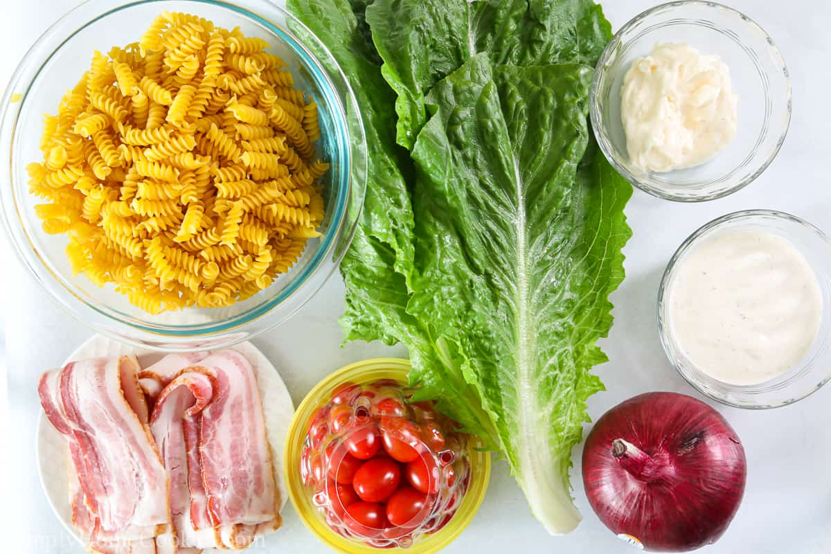 Ingredients for BLT Pasta Salad, including rotini pasta, romaine lettuce, cherry tomatoes, red onion, bacon, ranch dressing, and mayonnaise.