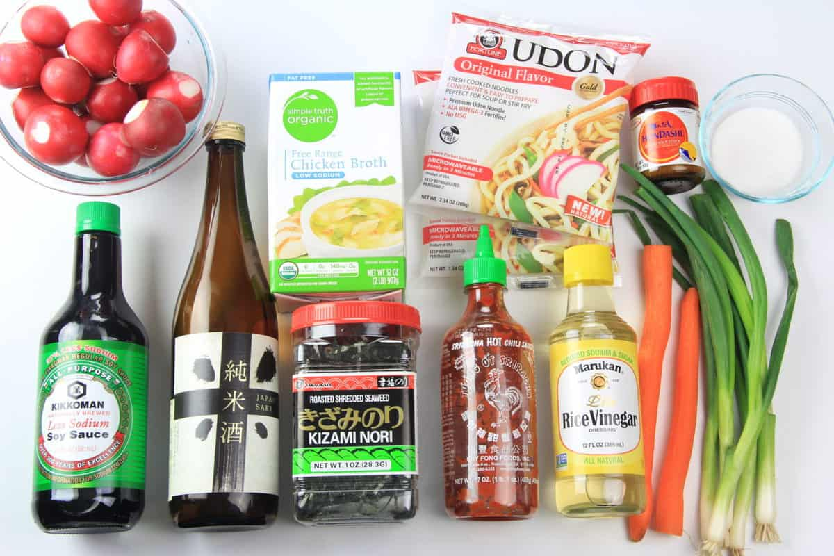 Ingredients to make udon soup, including soy sauce, sake, rice wine vinegar, Sriracha, radishes, udon noodles, carrots, green onion, hon-dashi powder, chicken stock, and seasoning.