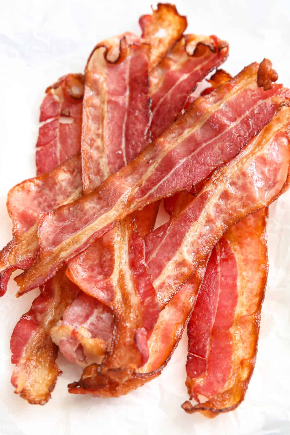 a pile of crispy bacon on a plate lined with paper towels