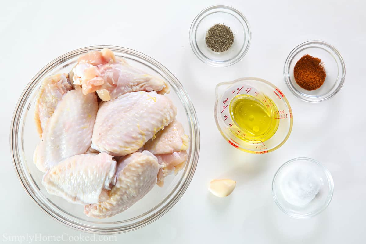 Ingredients for Air Fryer Chicken Wings, including raw chicken wings, oil, salt, pepper, paprika, and garlic.