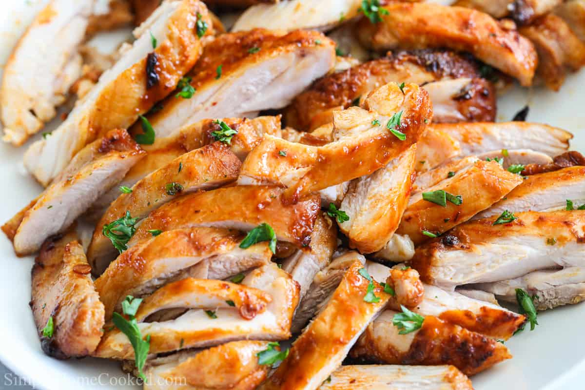 Close up of chipotle chicken thighs sliced into strips and garnished with parsley.