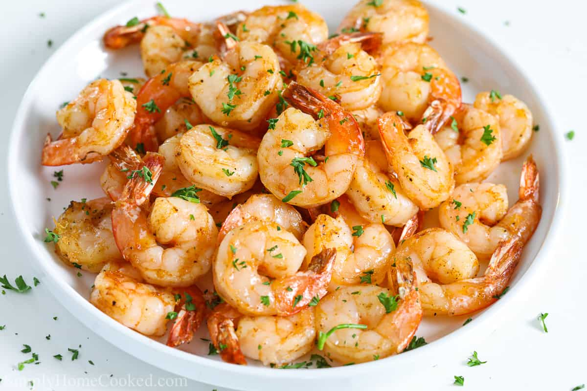 Bowl of Air Fryer Shrimp garnished with parsley and on a white background.