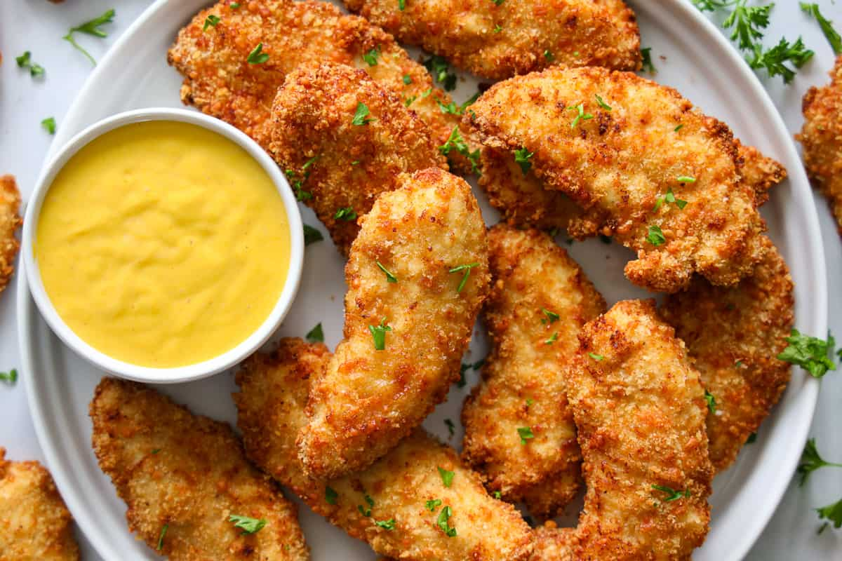 Plate of breaded air fryer chicken breasts with sauce on the side and a parsley garnish.
