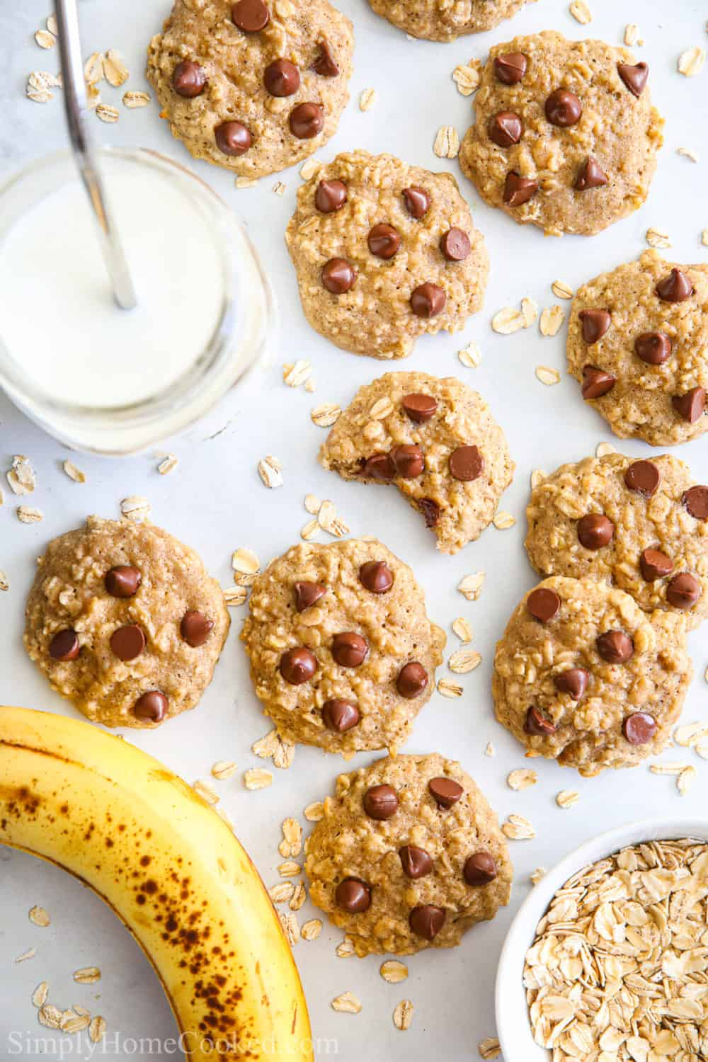 Chewy Banana Oatmeal Cookies with chocolate chips and a glass of milk and banana.