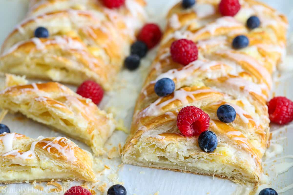 Two cheese danishes sliced and covered with berries on a white background.