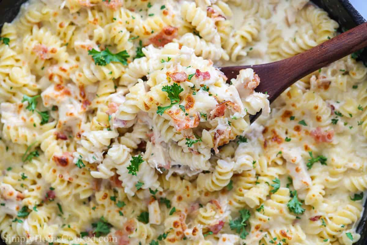 Skillet of Chicken Bacon Ranch Pasta and a wooden spoon.