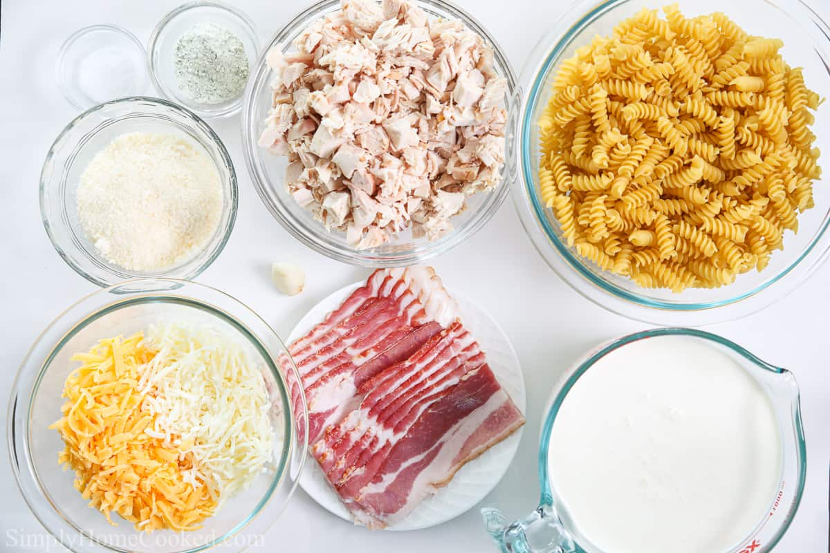 Ingredients for Chicken Bacon Ranch Pasta, including rotini pasta, bacon, shredded chicken, mozzarella, Parmesan, cheddar, salt, heavy cream, and ranch seasoning mix.