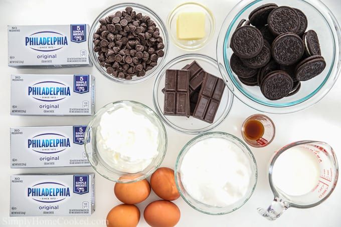 Ingredients for chocolate cheesecake bars, including cream cheese, chocolate chips, Oreo cookies, chocolate squares, sour cream, butter, vanilla, sugar, eggs, and heavy cream.