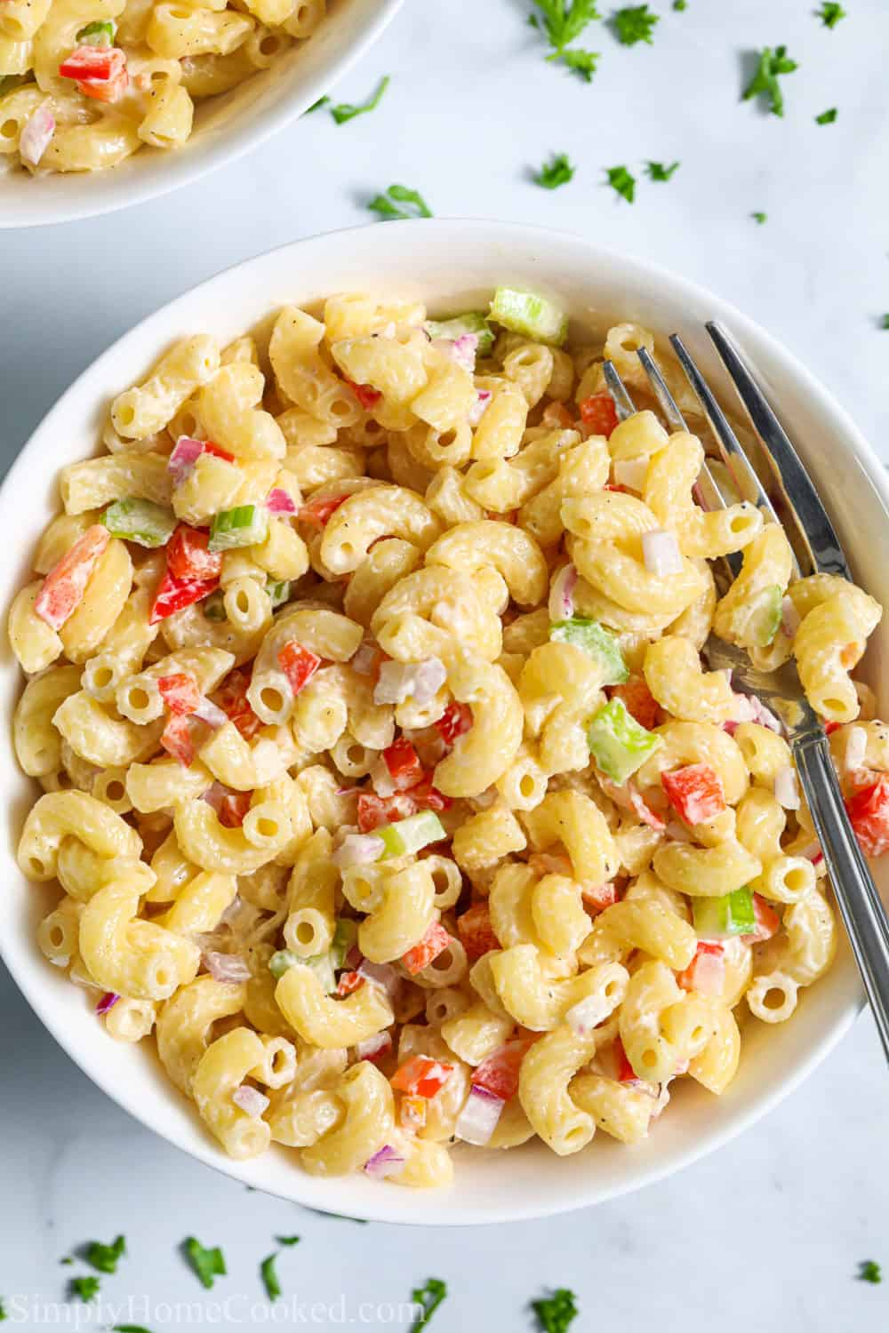 Bowl of Classic Creamy Pasta Salad with a fork in it and another bowl in the backgrround.