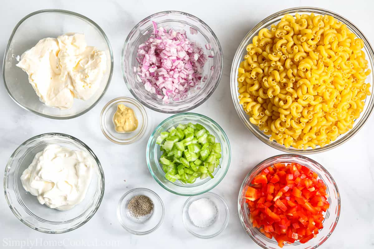 Ingredients to make Classic Creamy Pasta Salad, including mayonnaise, sour cream, dijon mustard, diced red onion, diced celery, diced red pepper, elbow macaroni, salt, and pepper.