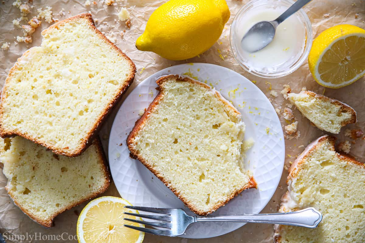 Slice of Moist Lemon Pound Cake on a white plate with a fork and some other slices of pound cake, icing, and lemons nearby.