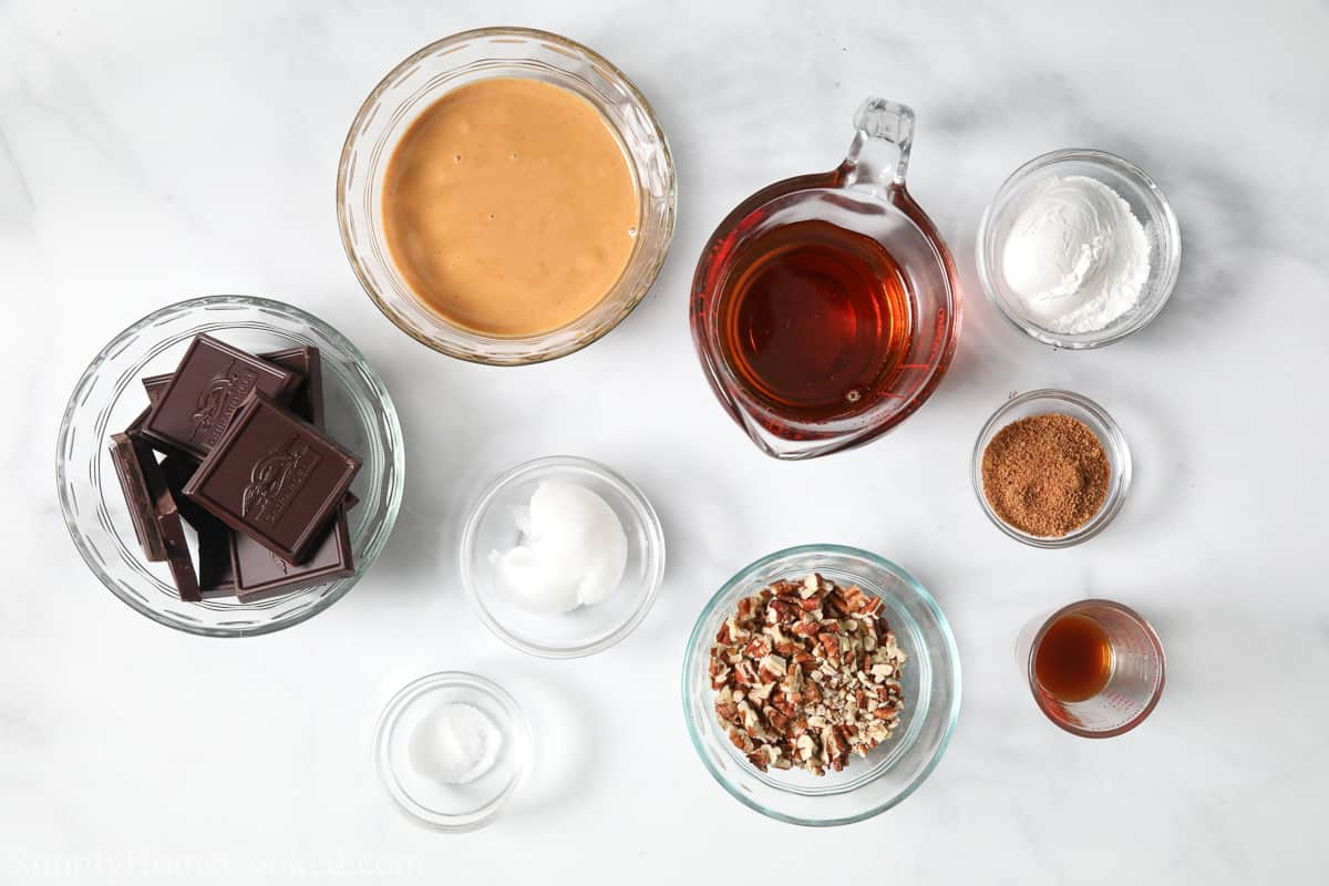 Ingredients for Paleo Chocolate Fudge, including baking chocolate, cashew butter, maple syrup, chopped pecans, coconut sugar, arrowroot powder, vanilla extract, sea salt, and coconut oil.