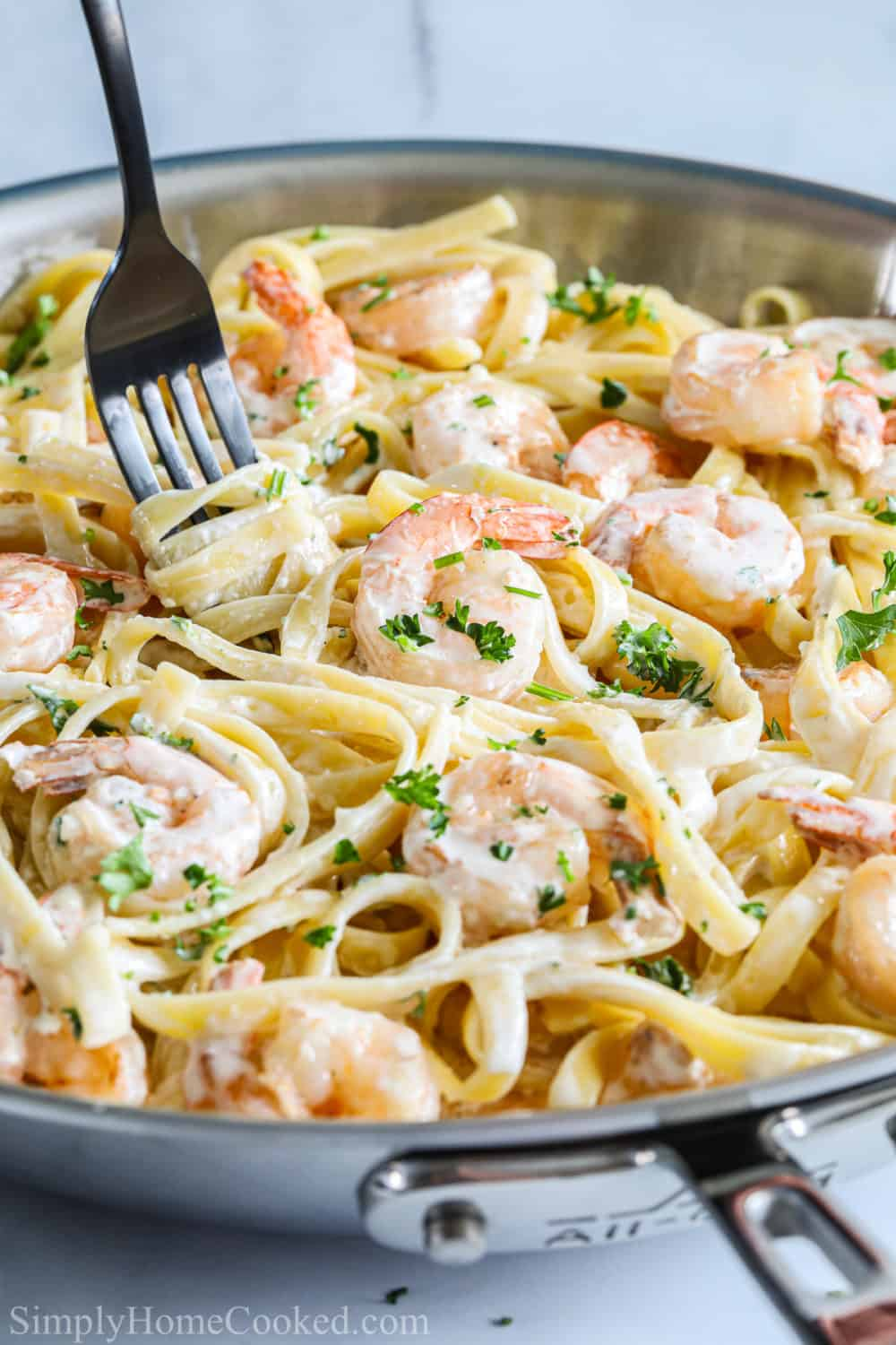 Shrimp Alfredo Pasta in a pan with a fork twirling the pasta.