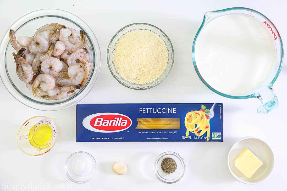 Ingredients for Shrimp Alfredo Pasta, including raw shrimp, fettucine pasta, Parmesan cheese, oil, butter, salt, pepper, heavy cream, and garlic on a white background.
