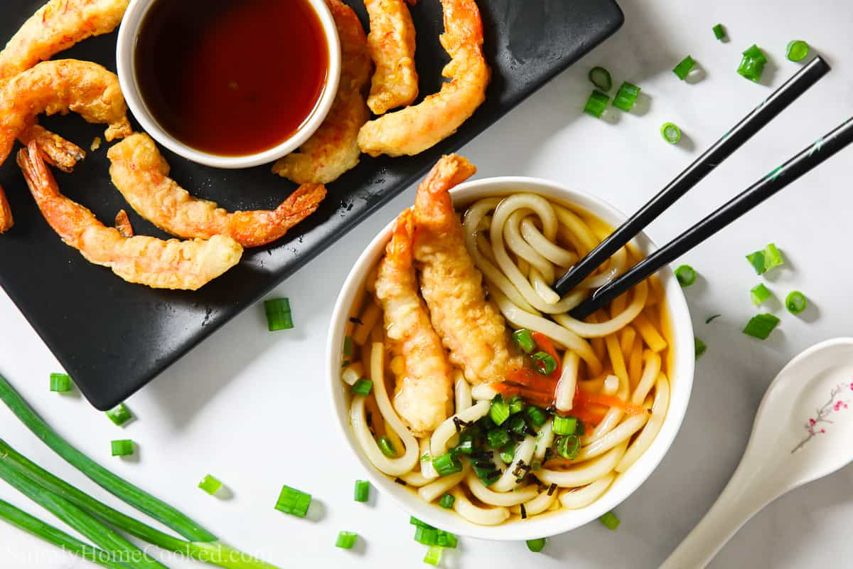 Bowl of udon soup with chopsticks and shrimp tempura in it, and a plate of shrimp tempura and dipping sauce to the side; green onions and a spoon next to them.