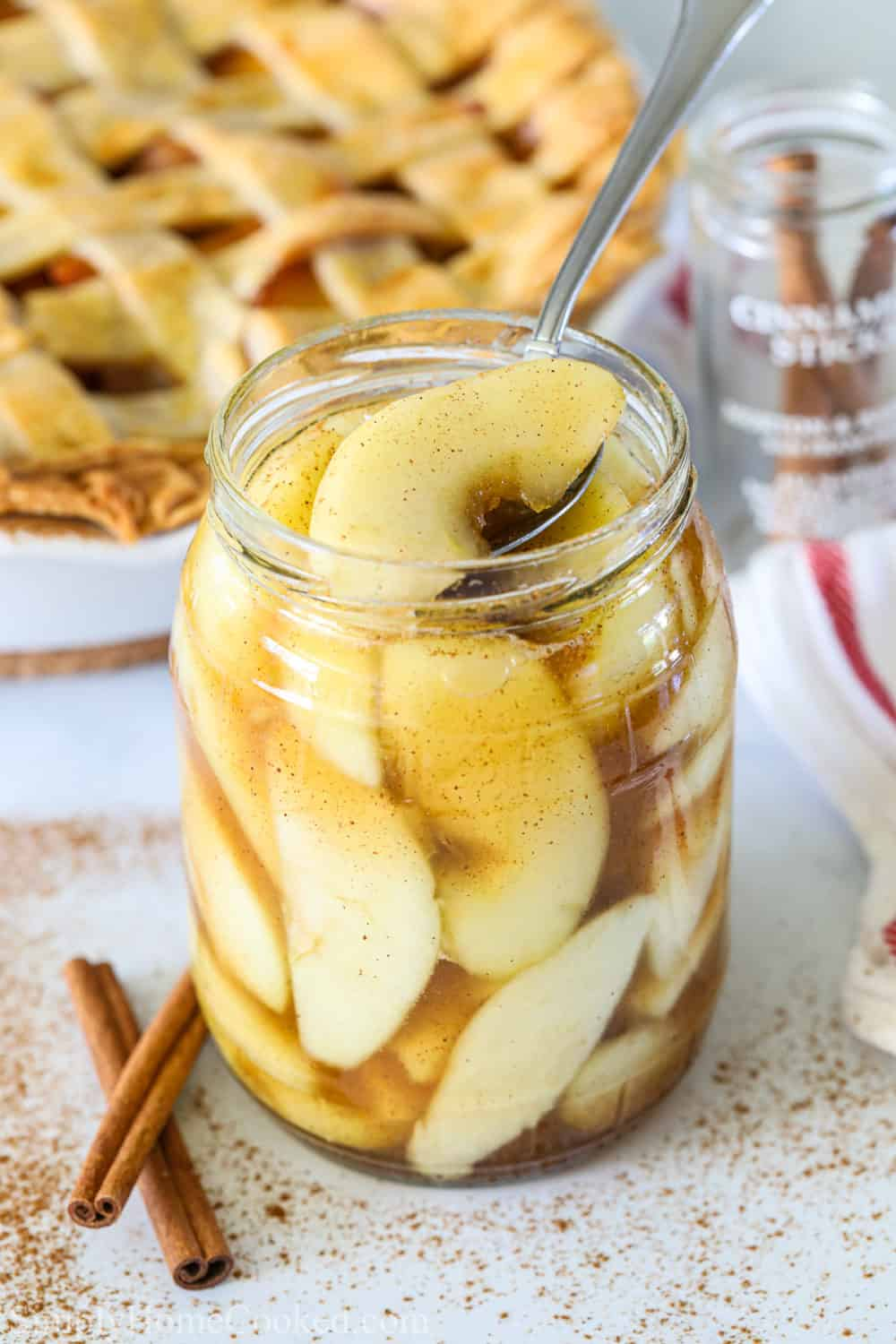 Close up of Easy Apple Pie Filling in a glass jar with a spoon and an apple pie and cinnamon sticks in the background.