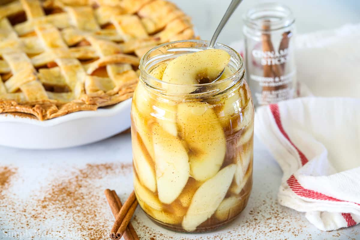 Easy Apple Pie Filling in a glass jar with a spoon and an apple pie, cinnamon sticks, and a white towel in the background.