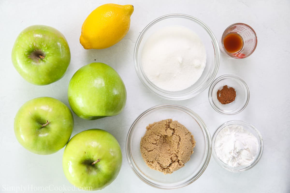 Ingredients for Easy Apple Pie Filling, including Granny Smith apples, lemon, brown sugar, granulated sugar, cornstarch, cinnamon, and vanilla extract, on a white background.