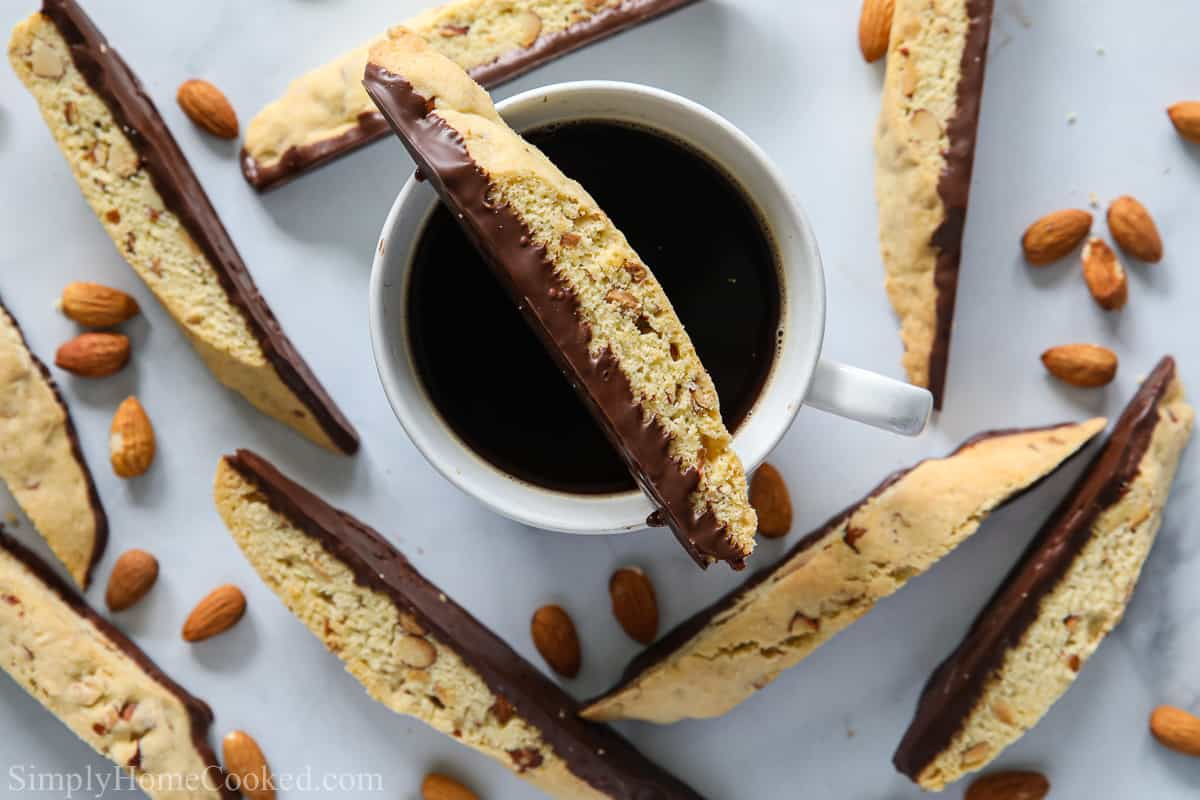Chocolate Dipped Almond Biscotti with almonds and a cup of black coffee.
