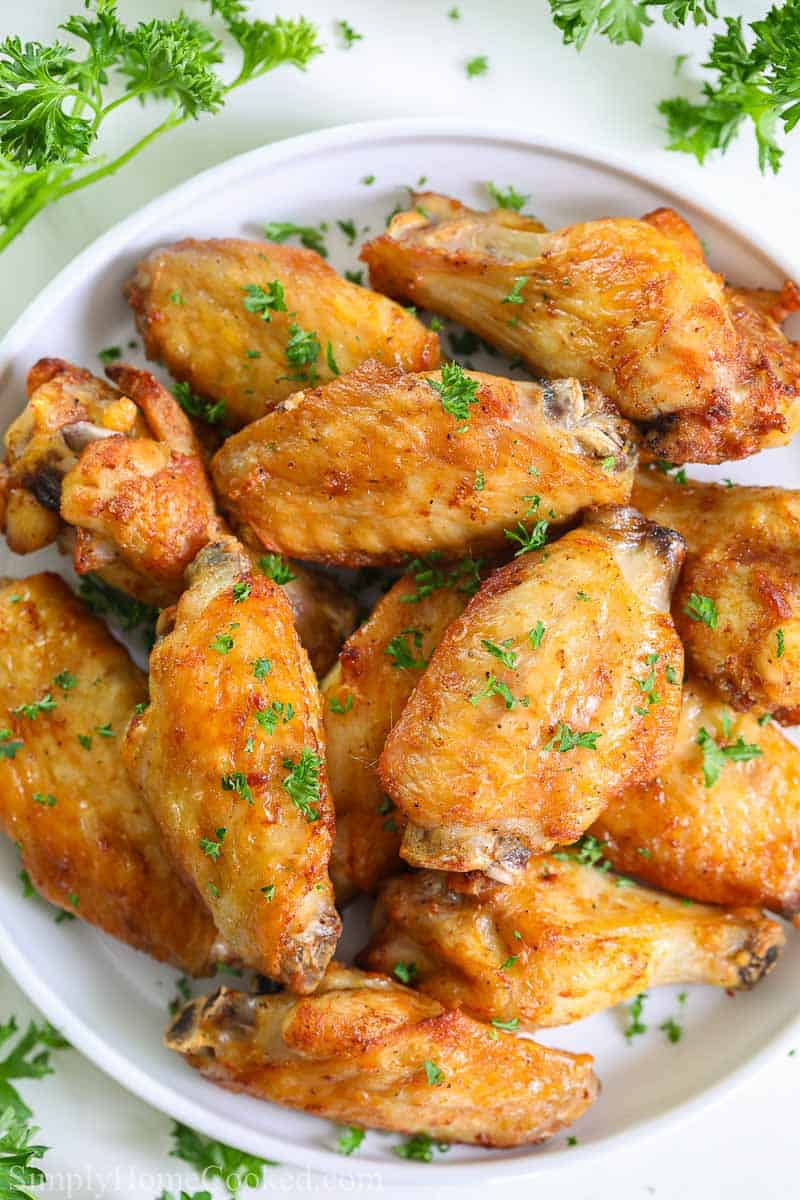 overhead image of crispy air fryer chicken wings on a white plate with chopped parsley on top