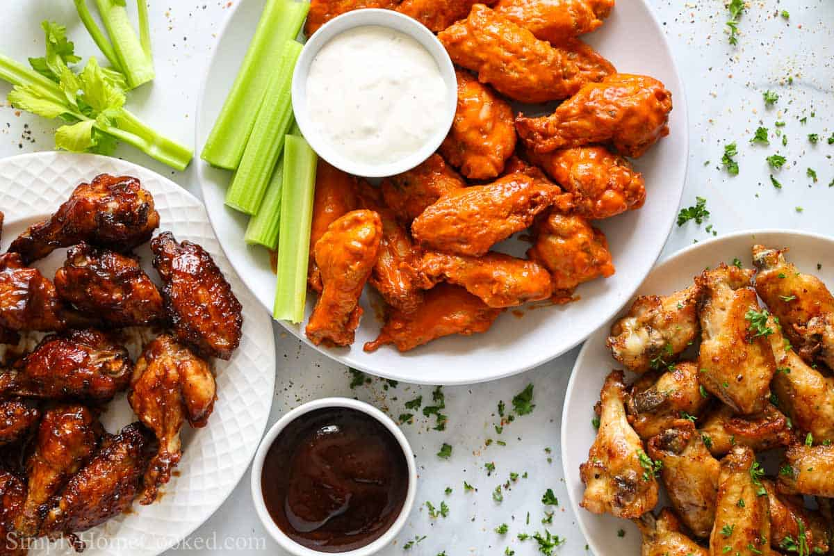 overhead image of bbq wings, buffalo wings, and lemon pepper wings on white plates
