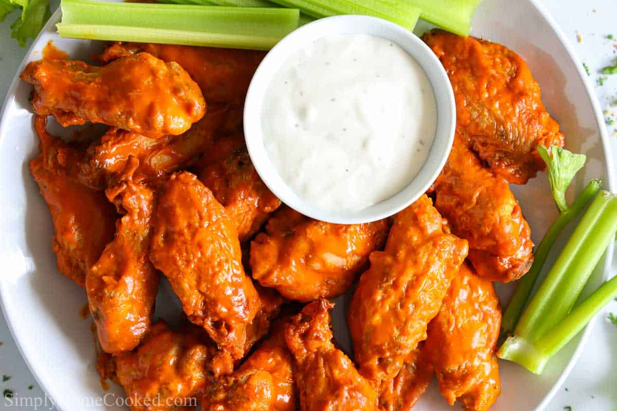 overhead image of air fryer buffalo wings on with ranch and celery sticks beside them