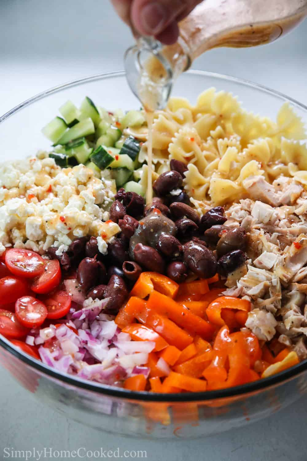 Greek dressing being drizzled over a bowl of Greek Chicken Pasta Salad.