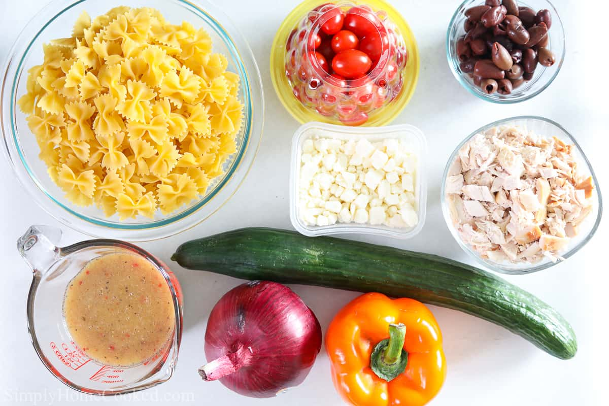 Ingredients for Greek Chicken Pasta Salad, including bowtie pasta, cherry tomatoes, kalamata olives, feta cheese, cucumber, chicken, red onion, bell pepper, and Greek dressing.