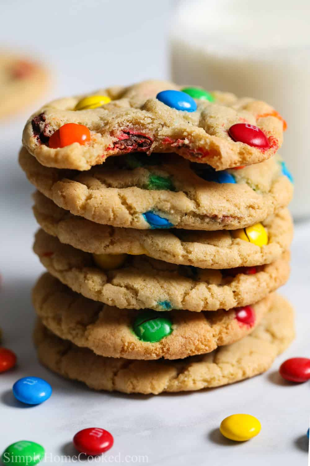 Stack of Chewy M&M cookies with some milk and M&M candies in background.
