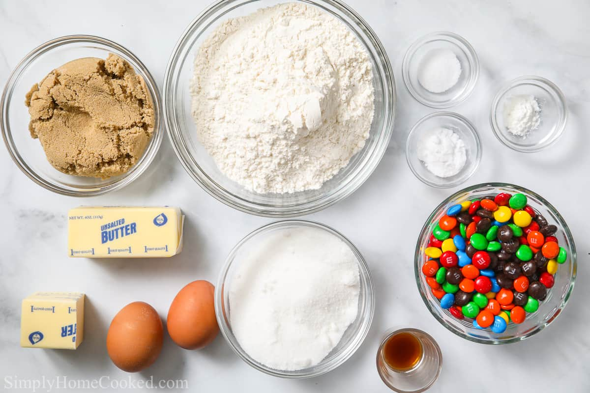 Ingredients for Chewy M&M Cookies, including flour, brown sugar, granulated sugar, cornstarch, baking soda, salt, butter, eggs, vanilla extract, and M&Ms.