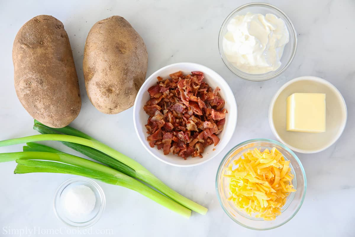 Ingredients for Air Fryer Baked Potato, including russet potatoes, butter, green onions, sour cream, bacon bits, shredded cheese, and salt.