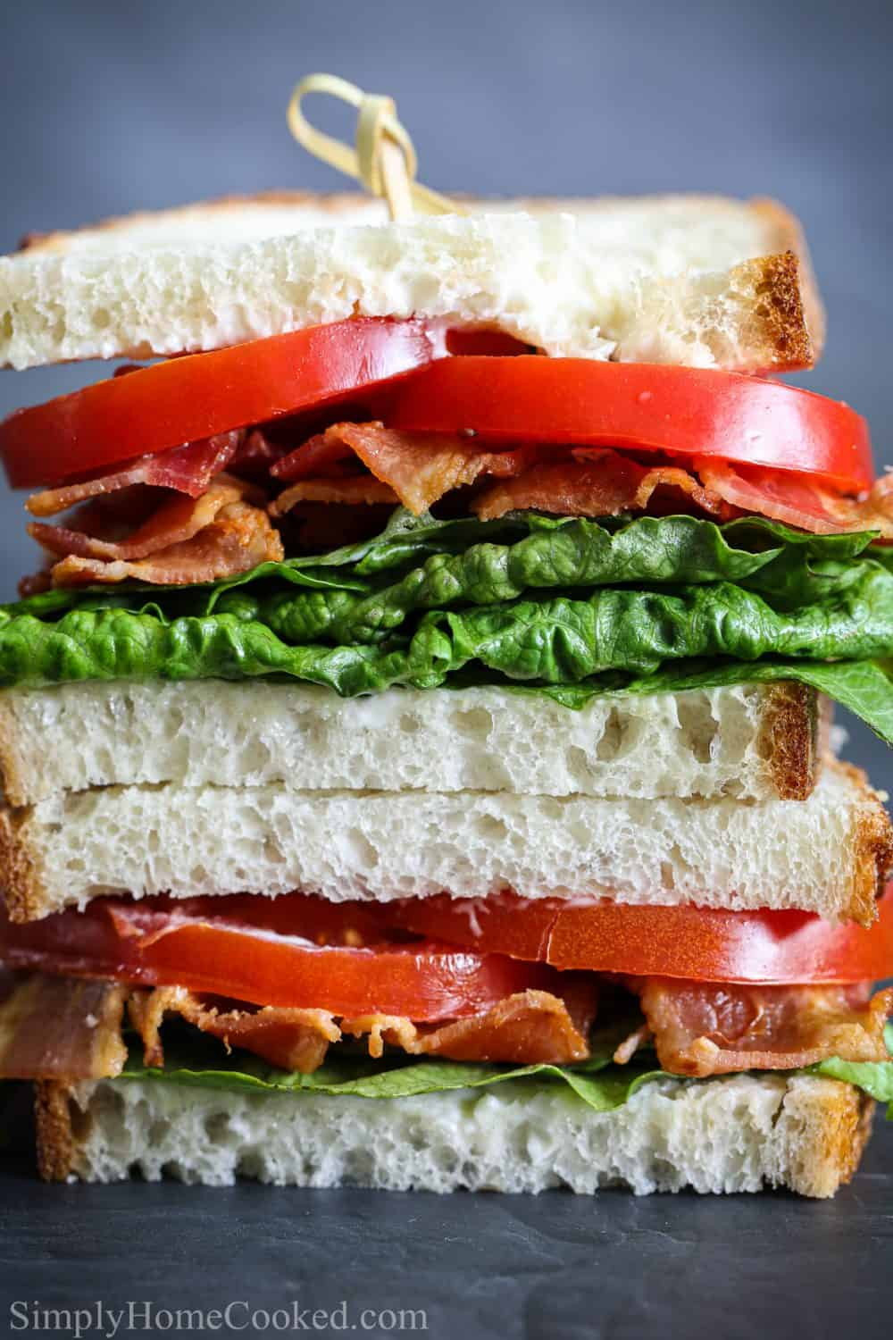 Close up of two halves of a BLT sandwich stacked up with a toothpick through the top.